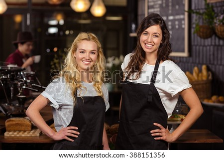 Pretty waitresses posing in front of the counter at the coffee shop - stock photo