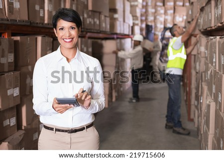 Pretty warehouse manager using calculator in a large warehouse