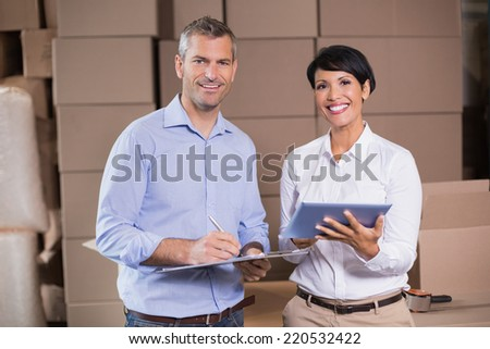 Pretty warehouse manager using tablet pc with colleague in a large warehouse - stock photo