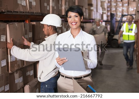 Pretty warehouse manager writing on clipboard in a large warehouse