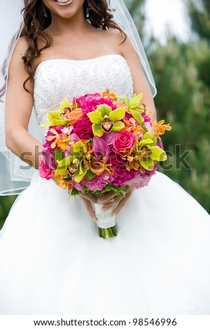 Pretty wedding bouquet held by a bride. Pink, Orange, and Green