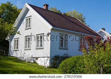 Pretty white Norwegian house and garden - stock photo