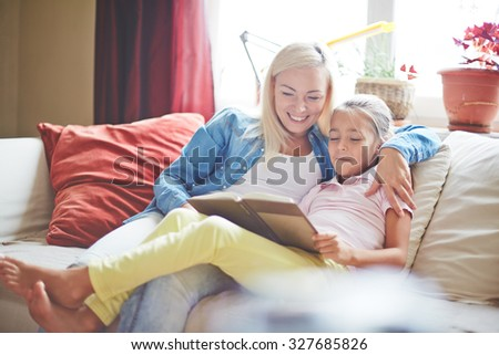 Pretty woman and little girl reading book at home - stock photo