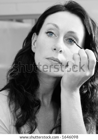 Pretty woman applying make up - stock photo