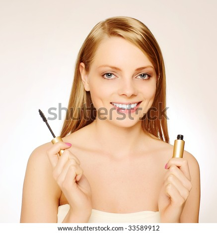 Pretty woman applying make up. - stock photo