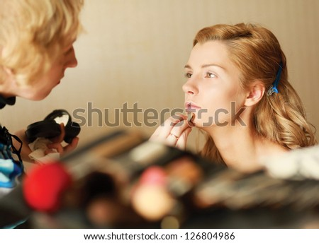 Pretty woman applying make up with brush - stock photo