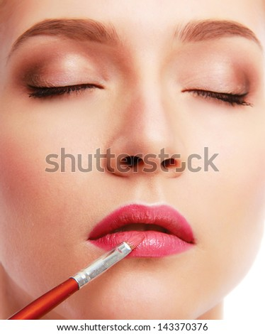 Pretty woman applying make up with brush