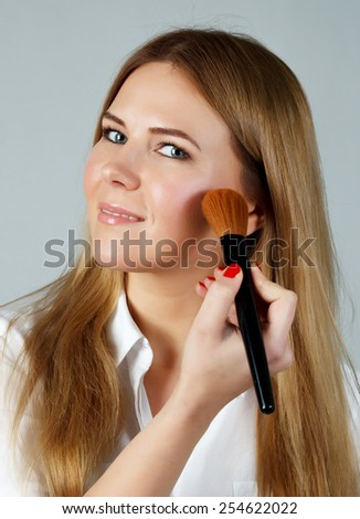Pretty woman applying make up with brush. gray background - stock photo