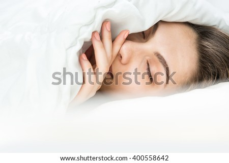 Pretty woman asleep under white blanket. Closed eyes. Sweet Dreams. Sleeping Beauty portrait. Relaxed time