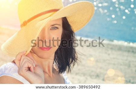 Pretty woman at the beach with a straw hat - stock photo
