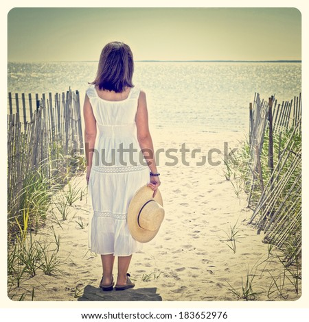Pretty woman at the beach with a straw hat with Instagram effect filter - stock photo