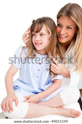 Pretty woman brushing her daugther's hair against a white background