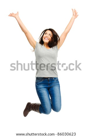 Pretty woman celebrates by jumping and cheering in studio, isolated on white - stock photo