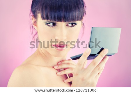 Pretty woman checking face skin, looking at mirror - stock photo