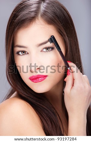 Pretty woman combing her eyebrow - stock photo