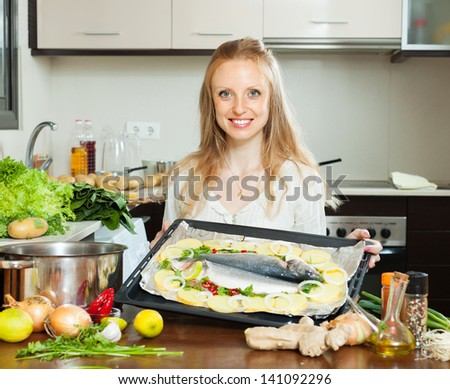 pretty woman cooking fish and potatoes in sheet pan - stock photo