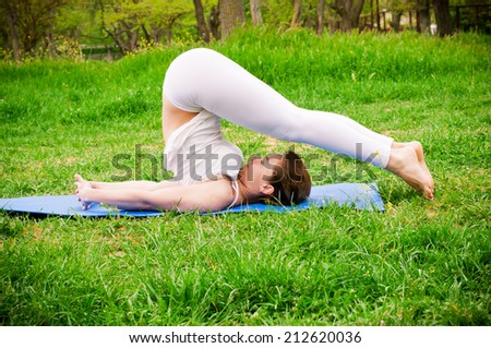 Pretty woman doing yoga exercises in the park. Concept of healthy lifestyle - stock photo