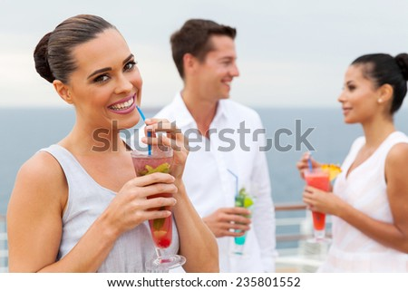 pretty woman drinking tropical juice with friends on background - stock photo