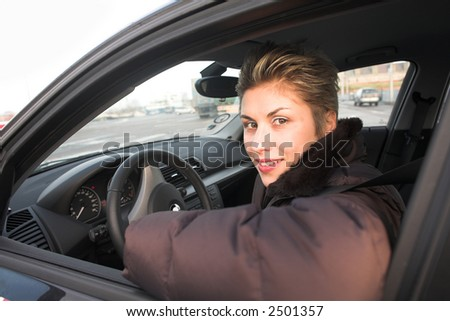 pretty woman driving a car hands on the wheel, looking at left side - stock photo