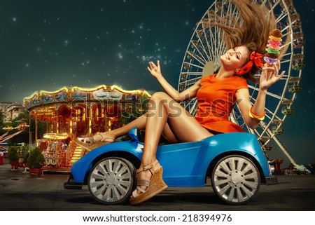 Pretty woman driving toy car holding ice cream and smile.  Amusement park at night - ferris wheel  in motion - stock photo