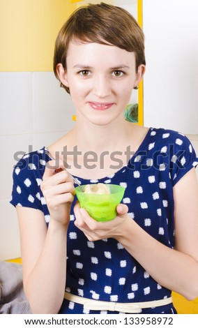 Pretty woman eating banana ice-cream in kitchen with dessert spoon - stock photo
