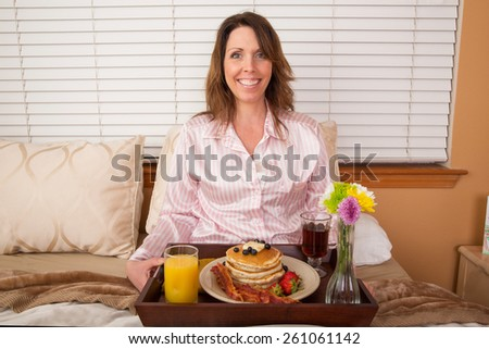 Pretty woman eating breakfast in bed - stock photo