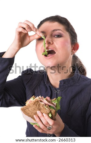 Pretty woman eating the salad of her healthy sandwich - stock photo