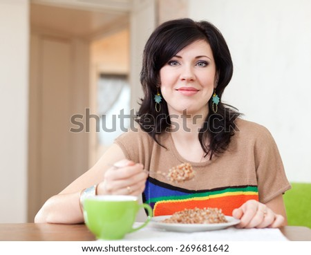 Pretty woman eats buckwheat cereal at home