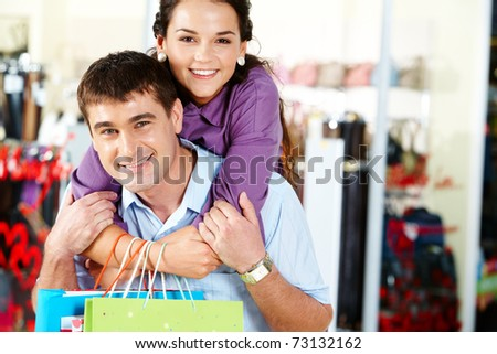 Pretty woman embracing happy man in the department store