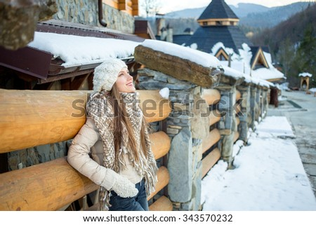 Pretty woman enjoy her winter vacation in mountain resort happy smiling and looking to the side - stock photo