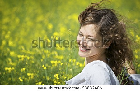 Pretty woman enjoying herself in yellow rapeseed field expressing happiness or freedom.
