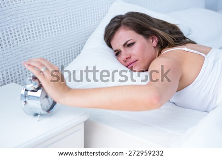 Pretty woman extending hand to alarm clock in bed at home in the bedroom - stock photo