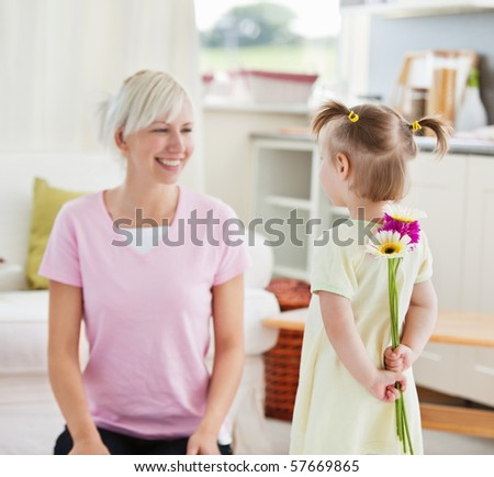 Pretty woman get surprise by her daughter in living room - stock photo