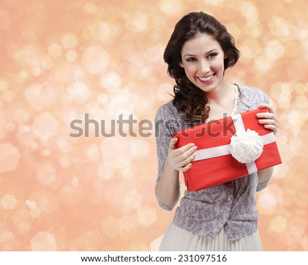 Pretty woman hands a present wrapped in red paper with white bow on gold light background - stock photo