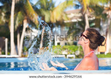 pretty woman having fun in luxury pool. remote tropical beaches and countries. travel concept - stock photo