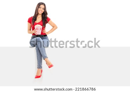 Pretty woman holding a box of popcorn seated on a blank panel isolated on white background - stock photo