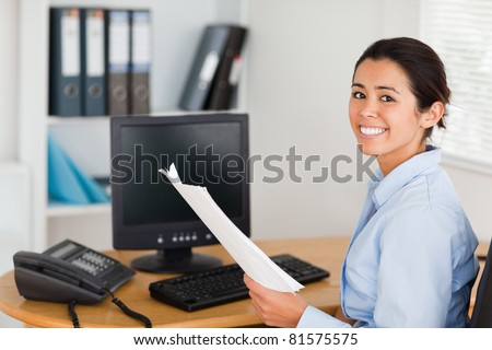 Pretty woman holding a sheet of paper and posing while sitting at the office - stock photo