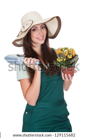 Pretty Woman Holding Plant And Gardening Shovel. Isolated On White - stock photo