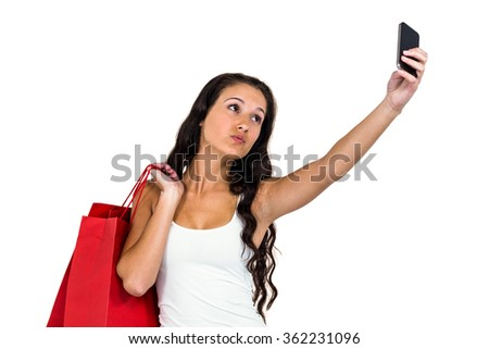 Pretty woman holding shopping bags taking selfie on white background - stock photo