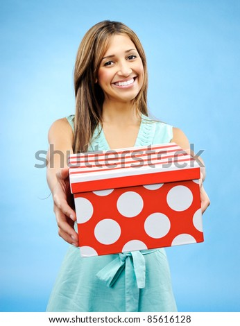 Pretty woman holds out a box to give a present for Valentine's Day - stock photo