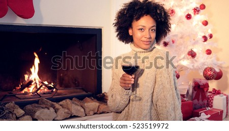 Pretty woman holds wine glass beside fireplace