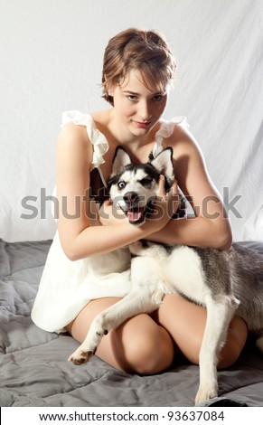 Pretty woman hugging her pet husky dog