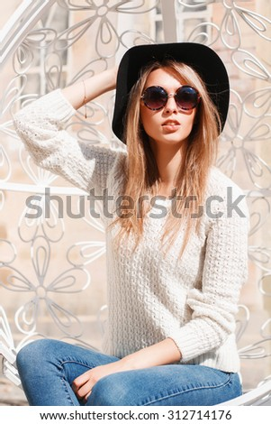 Pretty woman in a hat and sunglasses resting on a sunny day in a white suspended chair - stock photo