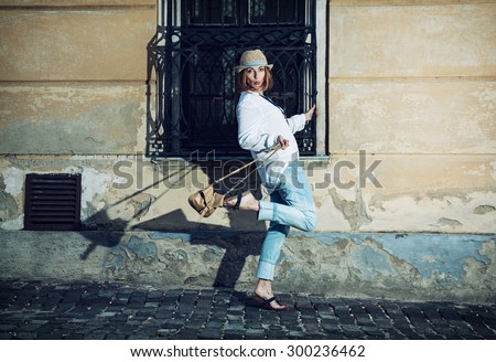 Pretty woman in a hat poses with a handbag and whistles in the courtyard. Beauty and fashion. - stock photo
