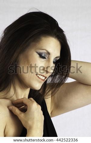 Pretty woman in a little black dress, looking pleased - stock photo