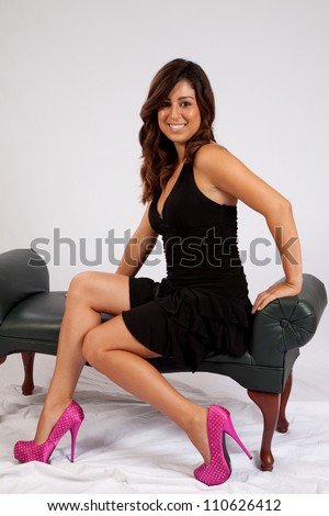 Pretty woman in a little black dress sitting on a bench and smiling at the camera with friendly pleasure and a sexy pose - stock photo