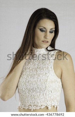 Pretty woman in a white dress,  looking thoughtful - stock photo