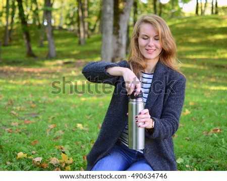 Pretty woman in an autumn park drinking tea