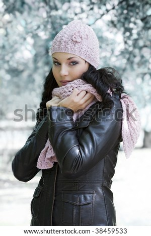 pretty woman in black jacket and pink scarf a winter day outside in park