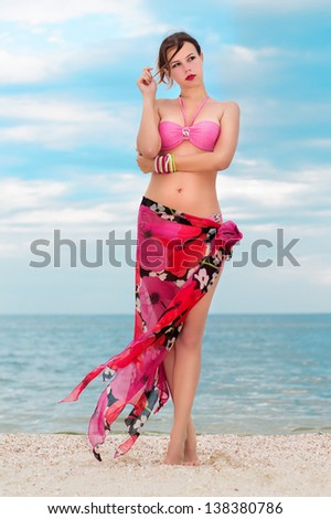 Pretty woman in flowered pareo posing on the beach
